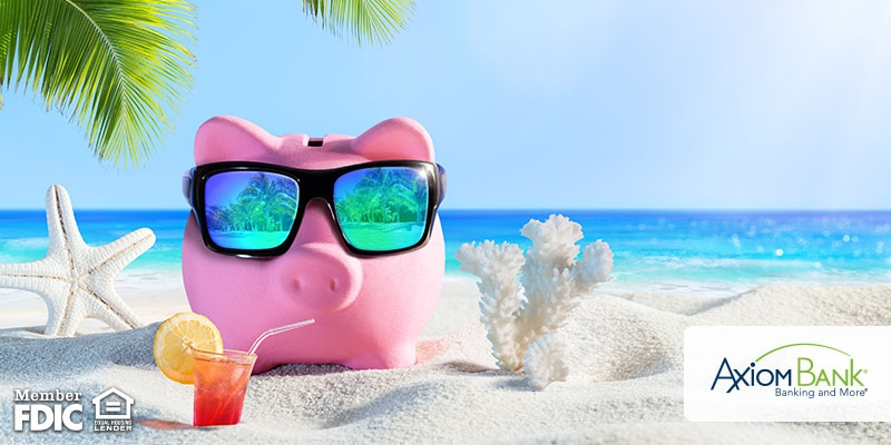Piggy bank sitting on the beach with sunglasses