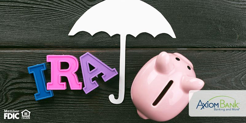 Letter blocks spelling IRA with umbrella and piggy bank