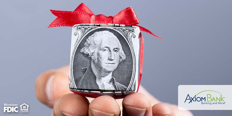 hand holding box made from money with red ribbon on top