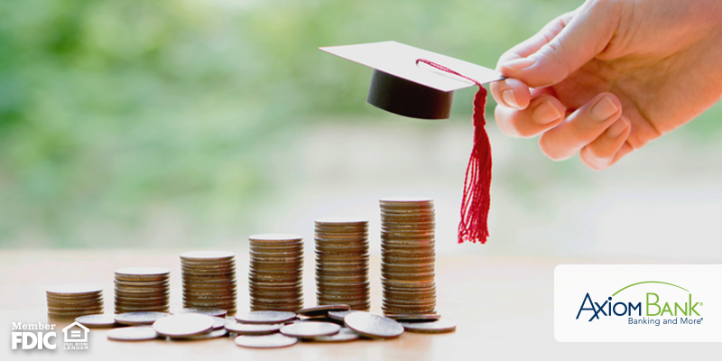 Stacks of coins on table and hand holding mini graduation cap