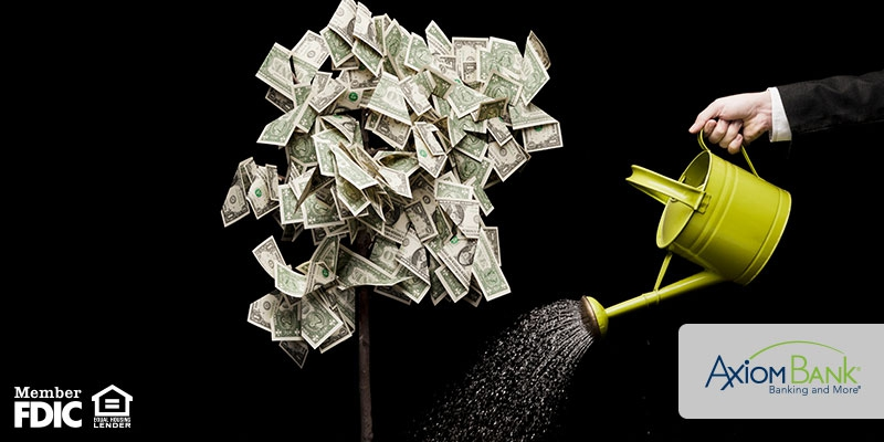 A hand with watering can watering money
