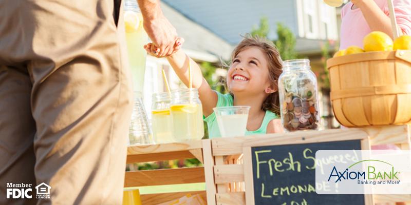 Little girl giving lemonade at lemonade stand